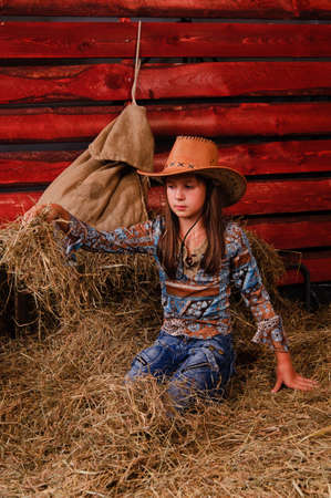 Girl in a cowboy hat in the hayloft photo