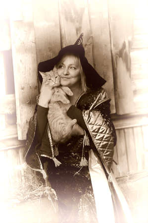 Witch with a red cat in her arms photo