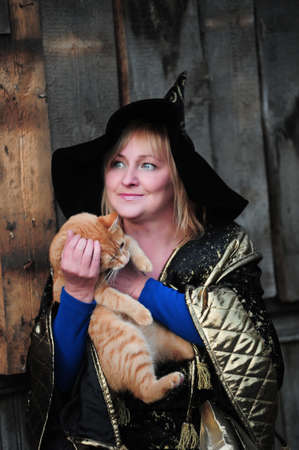 Witch with a red cat in her arms Stock Photo - 9070472