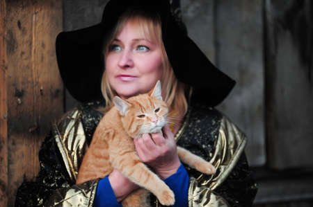 magick: Witch with a red cat in her arms Stock Photo