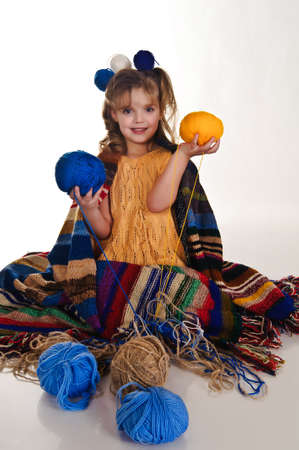 little girl with lots of balls of wool photo