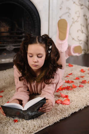 Girl with a book by the fireplace photo