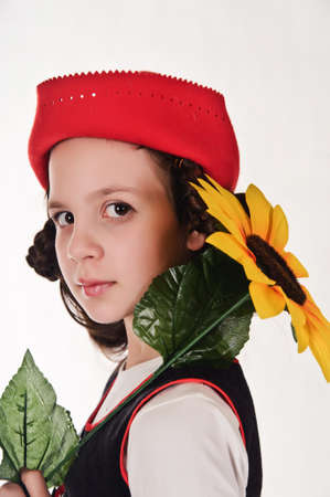 Girl in red hat with sunflower in their hands photo