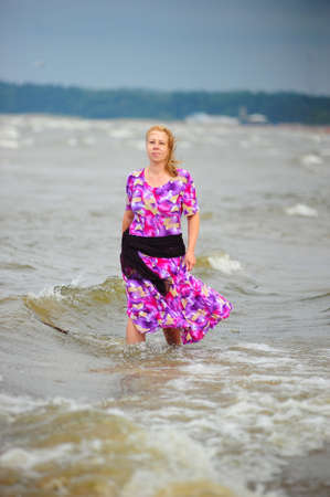 wet woman: woman walking in the water along the beach