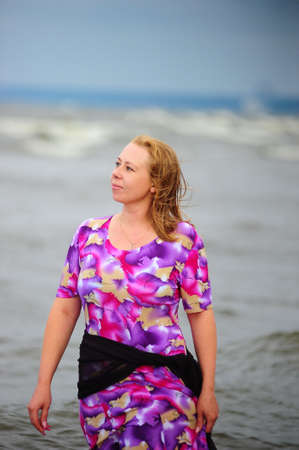 woman walking in the water along the beach photo