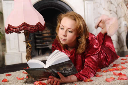 woman reading a book on the carpet by the fireplace Stock Photo - 8934765