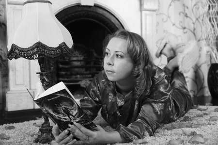 woman reading a book on the carpet by the fireplace photo