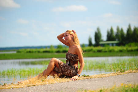 long lake: girl sitting on the shore of the lake