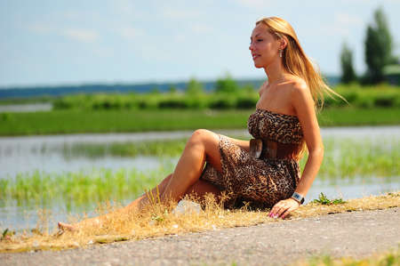 girl sitting on the shore of the lake