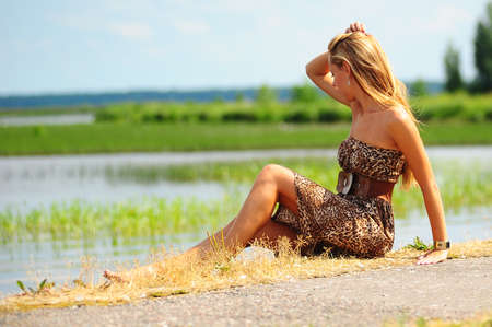 girl sitting on the shore of the lake photo