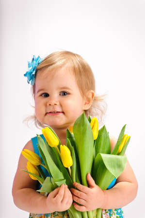 little girl with a bouquet of yellow tulips photo