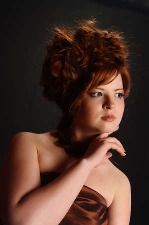 The elegant red-haired girl in studio photo