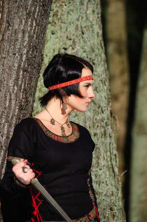 vestido medieval: Retrato de la chica con un cuchillo en un vestido medieval