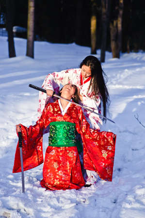 demure: two girls in Japan Kim fighting with swords Stock Photo