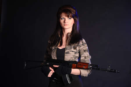 Young and sexy woman holding a rifle photo