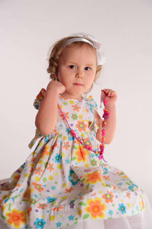 tries: The little girl tries on a beads Stock Photo