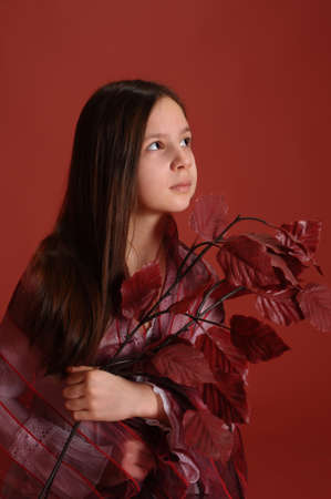 girl wearing a scarf with autumn leaves in the hands of photo