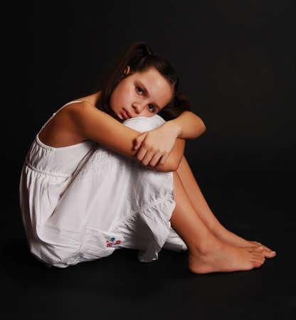 falda corta: chica triste sentado sobre un fondo negro