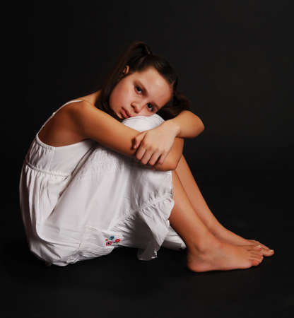 young girl feet: sad girl sitting on a black background