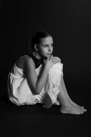 sad girl sitting on a black background Stock Photo - 9723185