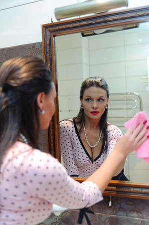 woman wash the mirror and looking into it Stock Photo - 9722402