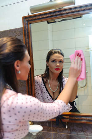 woman wash the mirror and looking into it photo