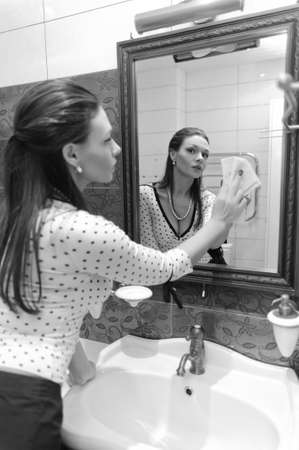 woman wash the mirror and looking into it Stock Photo - 9722403