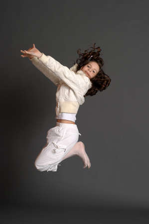 girl in white dress jumping in studio photo