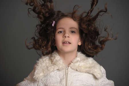 hair tied: girl in white dress jumping in studio