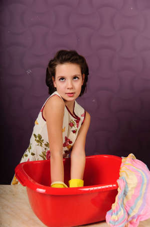 Girl wash clothes in a bucket photo