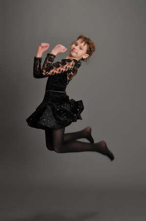 girl jumping high in the studio on a gray background photo