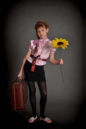girl with an old suitcase and a sunflower Stock Photo - 9382546