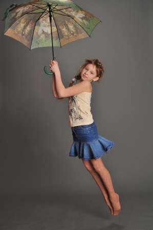 Girl with umbrella jumping photo