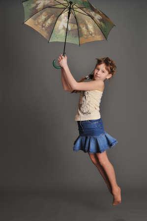 Girl with umbrella jumping Stock Photo - 9381496