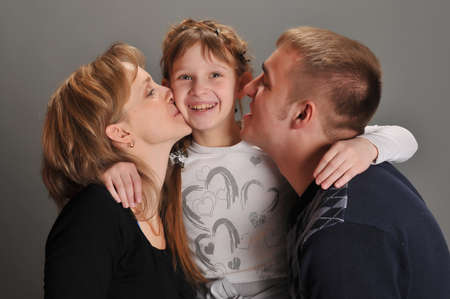 Parents kissing daughter  photo