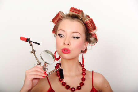 A housewife with hair-curlers and with a magniglass photo