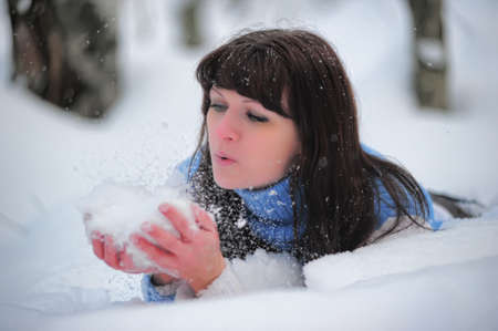 The young woman with snow in hands photo