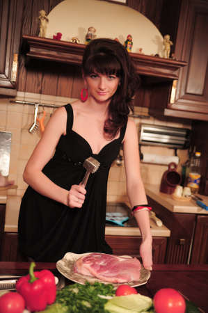 beautiful young woman preparing food in the kitchen photo