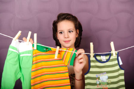 houseclean: Young housewife hanging clothes on clothesline Stock Photo