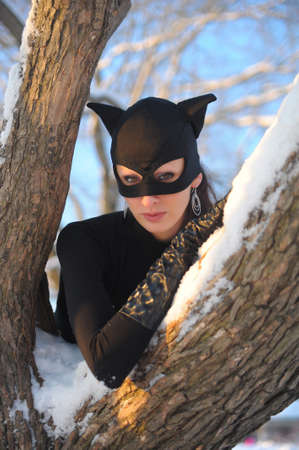 Beautiful young woman wearing catsuit and mask photo