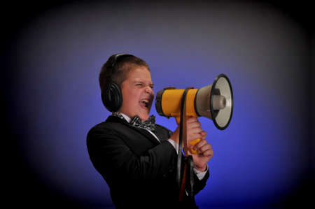 miffed: boy screaming at the loudspeaker Stock Photo