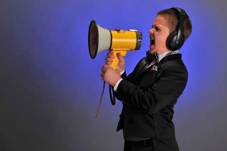 grouchy: boy screaming at the loudspeaker Stock Photo