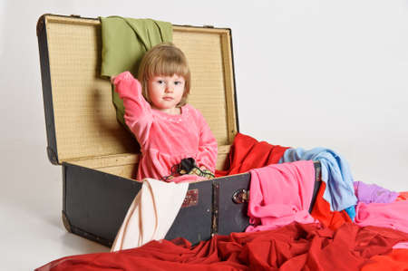 messy clothes: little girl and an old suitcase