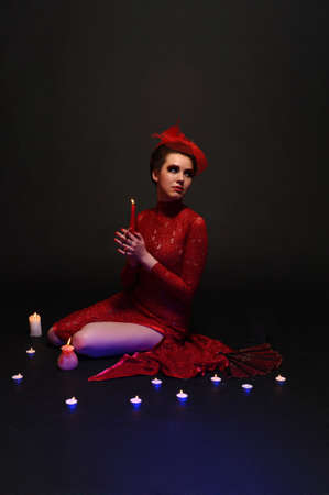 woman in red dress surrounded by candles photo