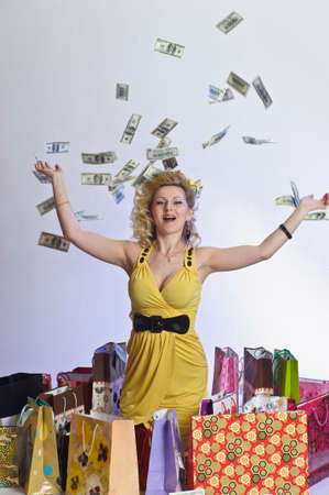 gastos: young woman with shopping and money Imagens