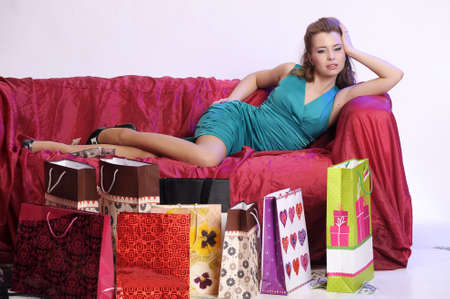 girl resting on the couch after shopping bags next to the shopping photo