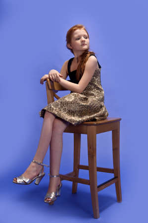 Red-haired girl sitting on a high chair photo