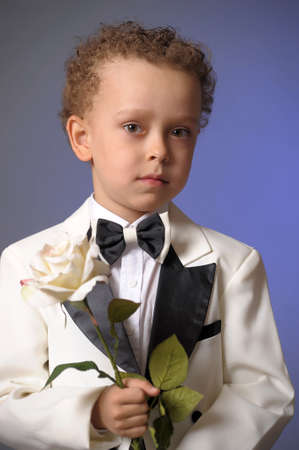 making music: boy in a frock coat with a white rose