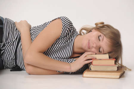 student sleeping on a pile of books photo