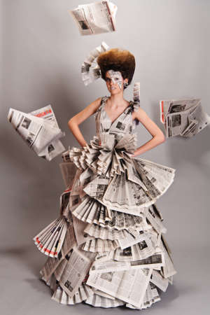 Portrait of a beautiful girl in a newspaper dress photo